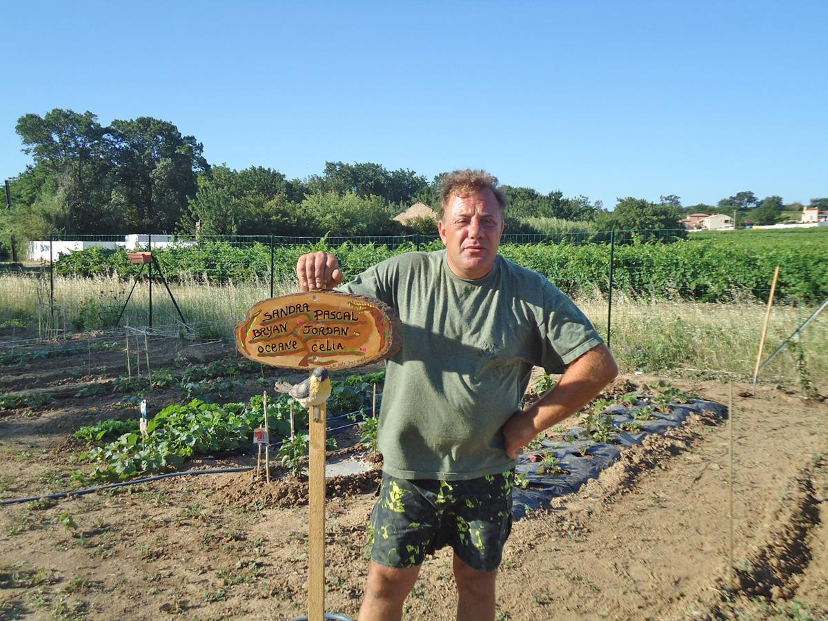 Pascal IROLLA devan la pancarte de son Jardin
