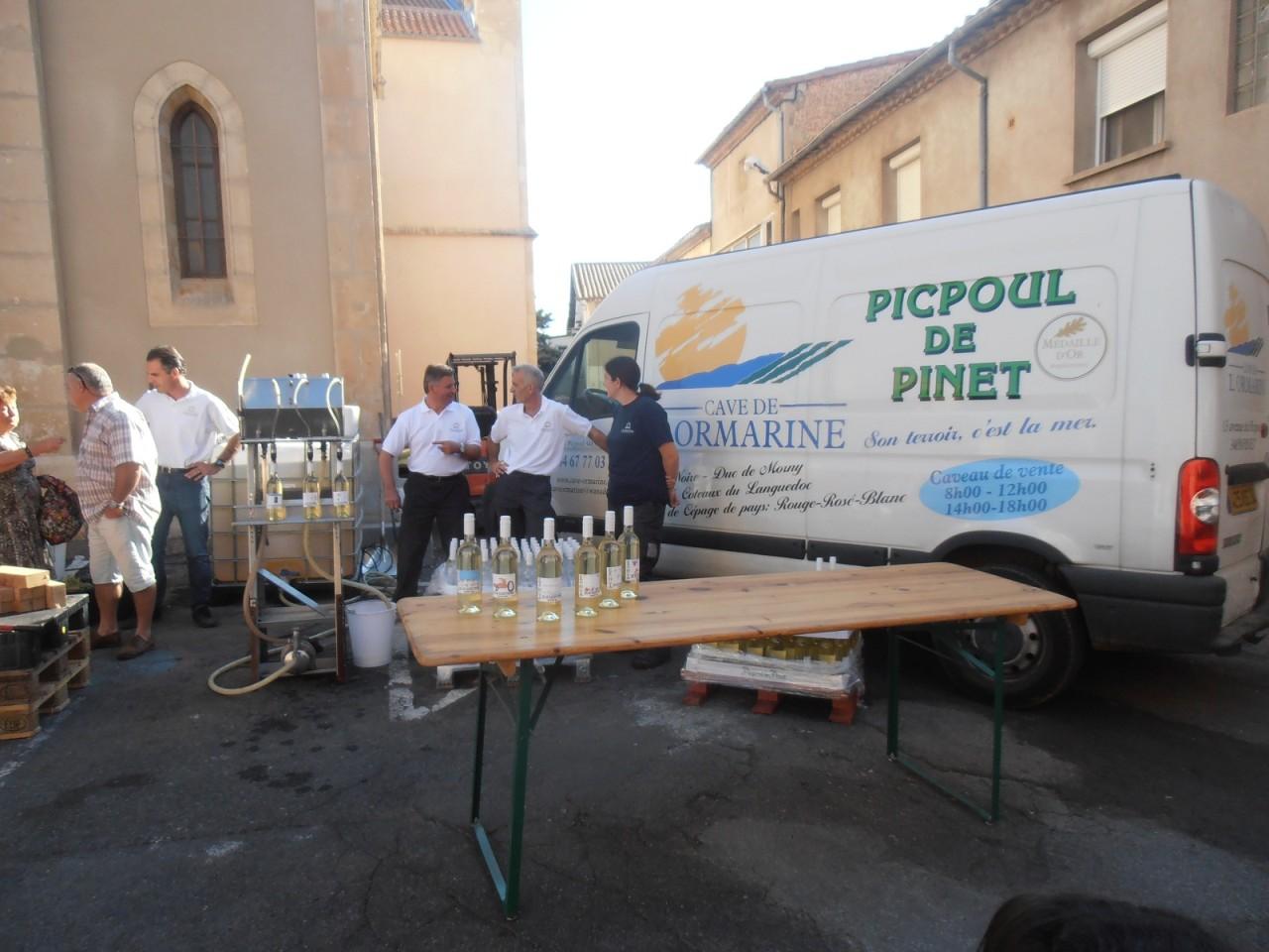 Vente de jus de raisin devant l'Eglise par la Cave de l'Ormarine ---- Cyril PAYON  (Directeur de la cave) et ses adjoints ---- 1 euro la bouteille 200 bouteilles vendues